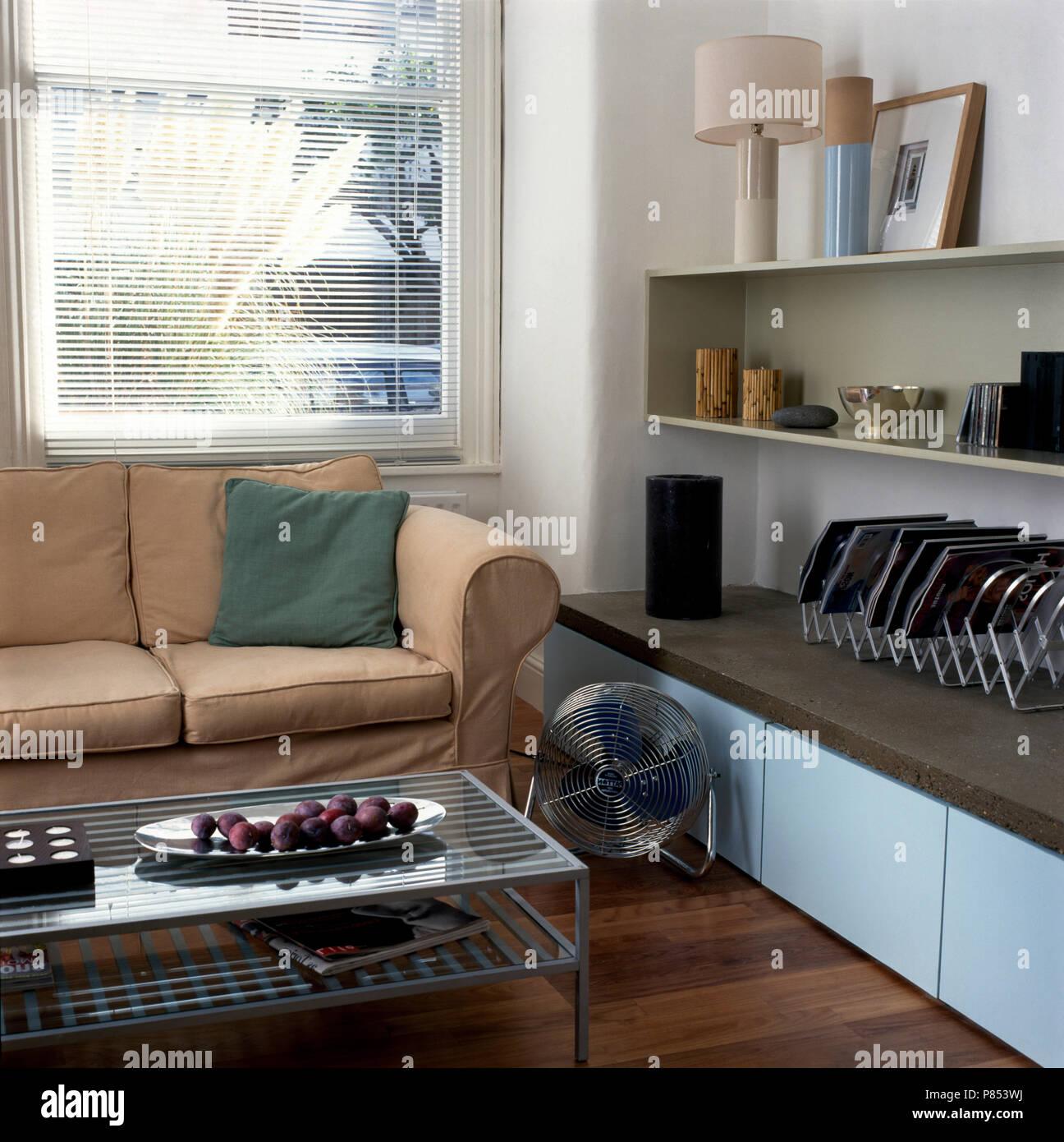 Cromo ventilatore elettrico tra un divano beige e ripiani a ...