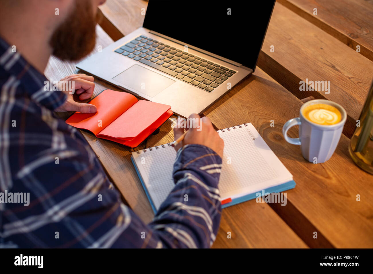 Immagine ritagliata di casual uomo d affari o la pianificazione del freelancer il suo lavoro sul notebook, lavorando sul computer portatile con smart phone, una tazza di caffè sul tavolo al coffee shop o home office. Immagini Stock