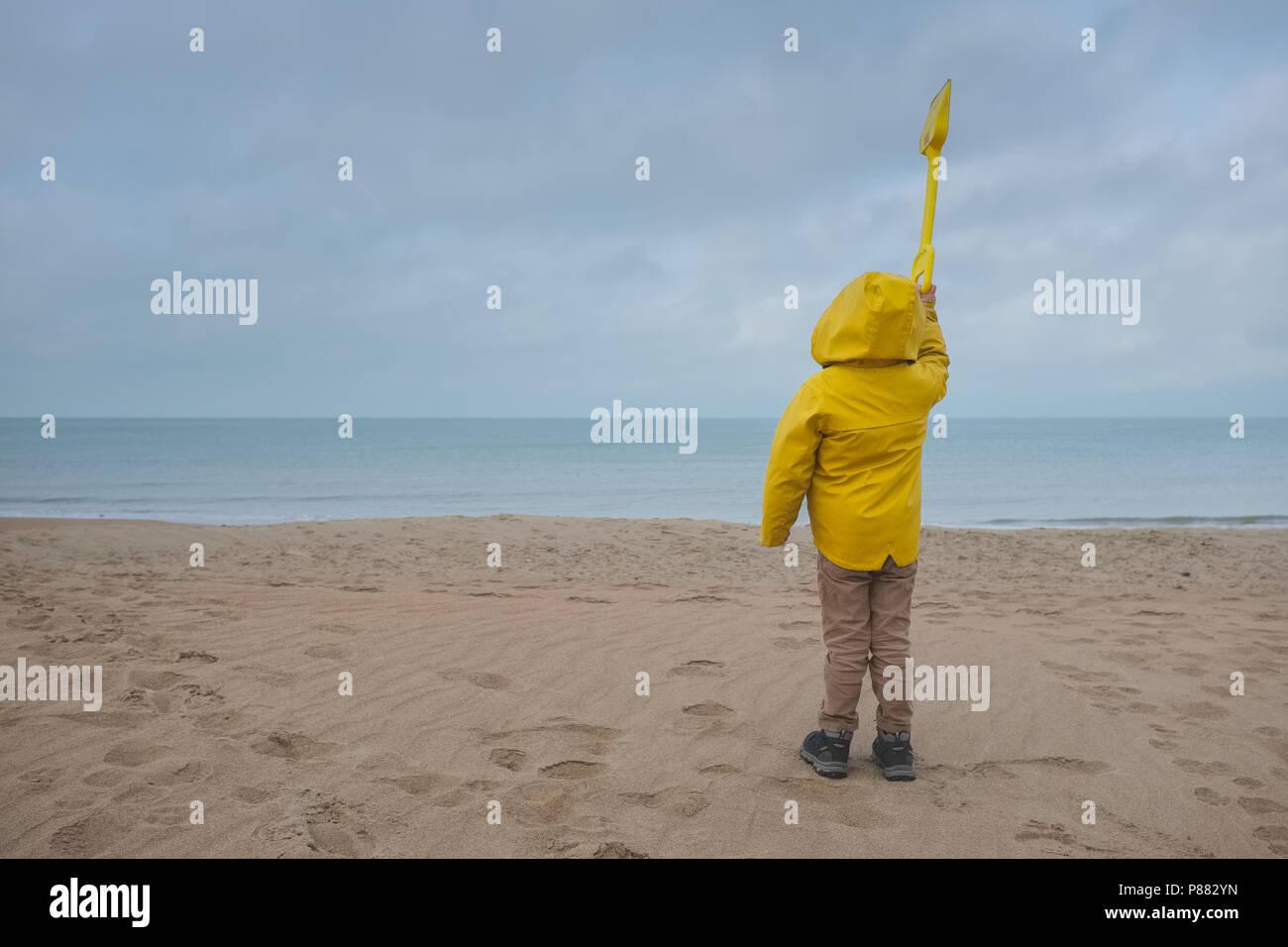 Donna su un giallo Giacca pioggia guardando al mare con