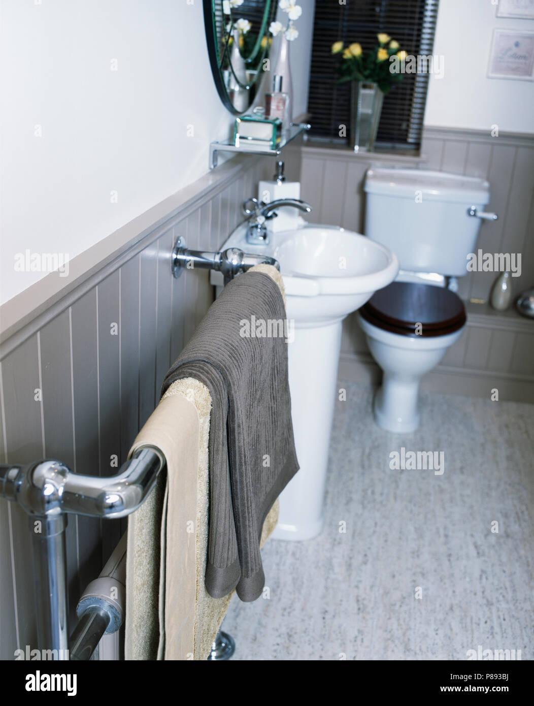 Beige e grigio asciugamani su chrome towel rail contro la linguetta+ ...