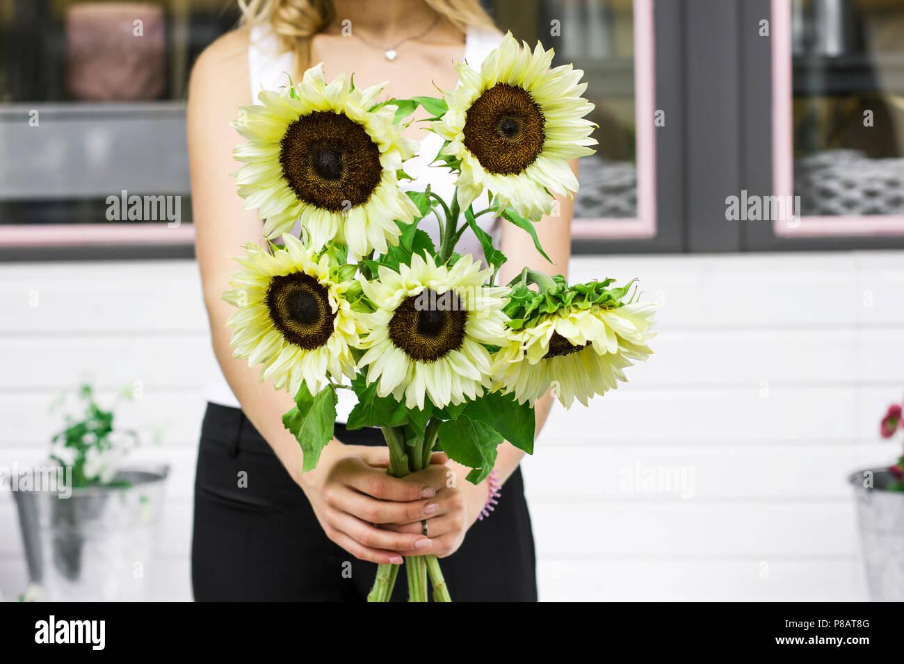 Giovane donna azienda luci decorative giallo dei girasoli nella