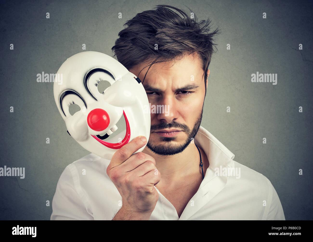 Giovane uomo barbuto holding maschera felice e la sensazione di essere triste e deprimente mentre guardando la fotocamera su sfondo grigio Immagini Stock