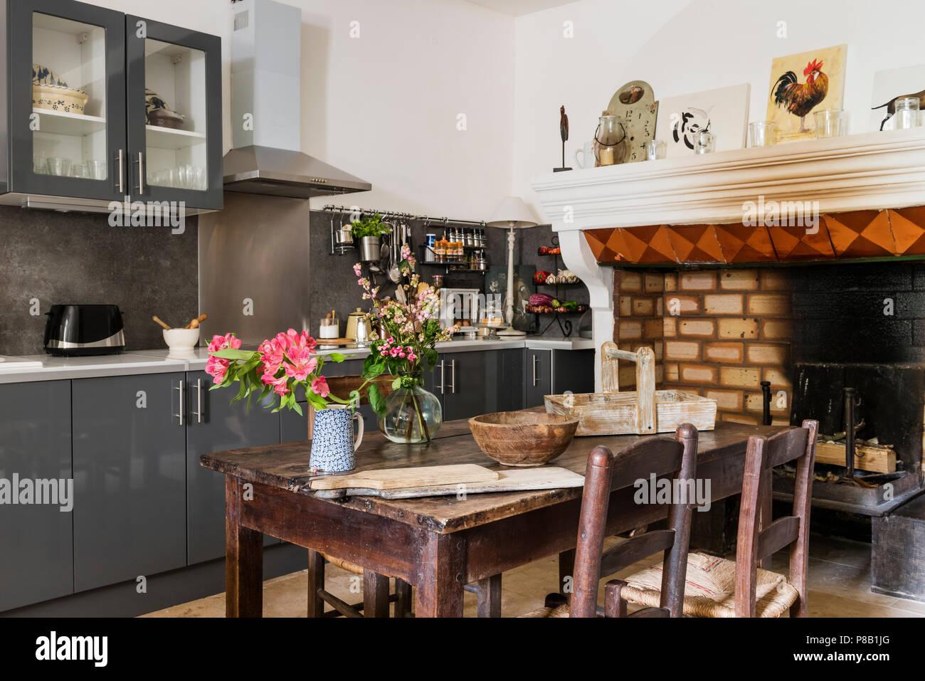 Cucina moderna con antico camino trattenuto. Xix secolo tavolo e ...