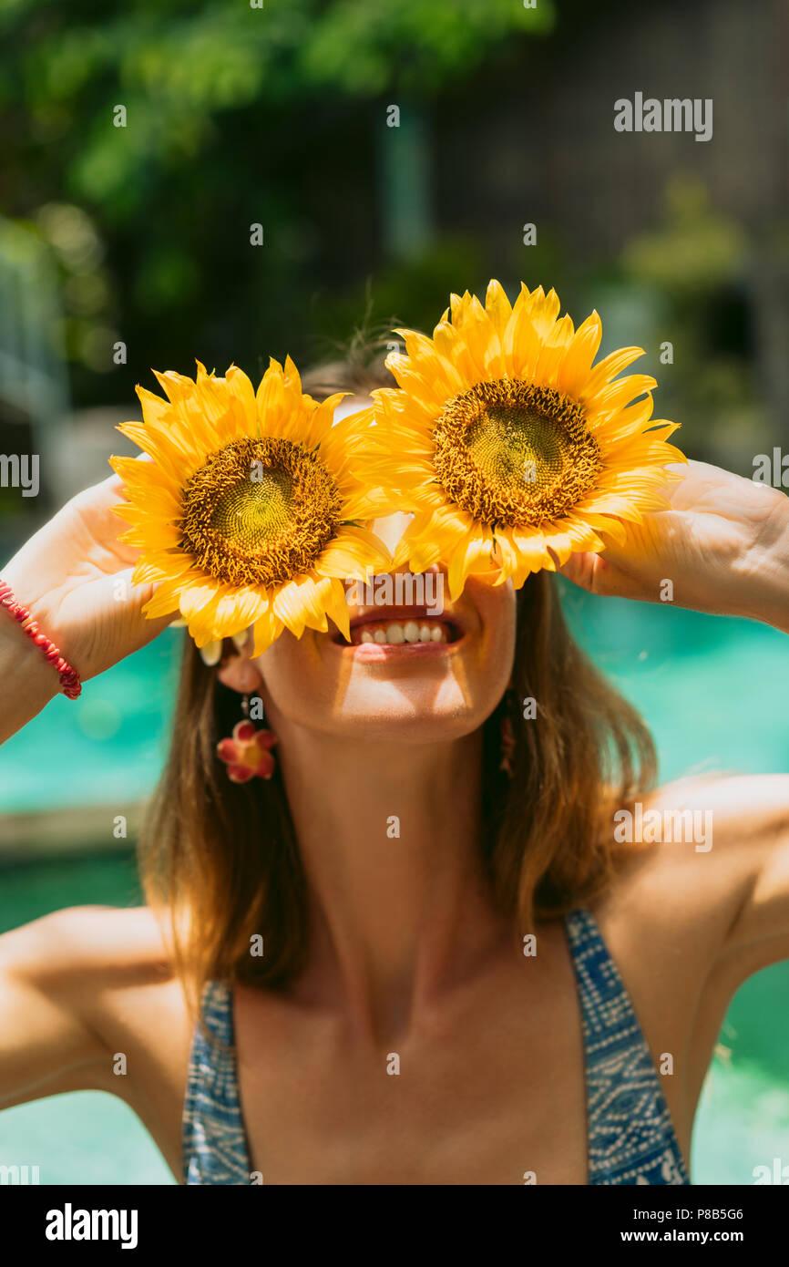 Bella ragazza sorridente in bikini azienda girasoli a giornata di sole Immagini Stock