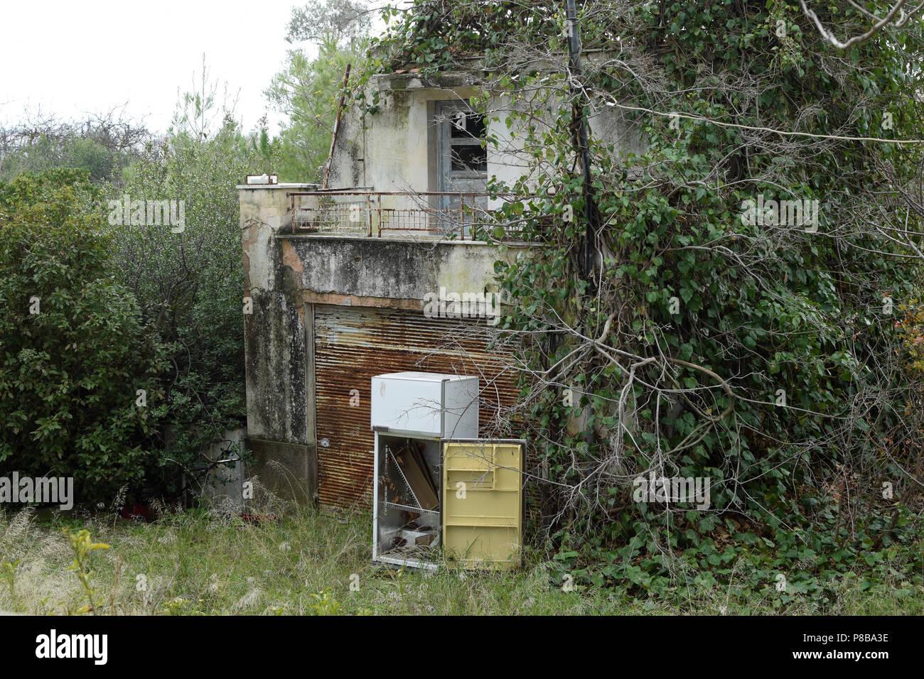 Casa abbandonata superamento da parte della natura e scartato frigo in giardino con piante sovradimensionate. Foto Stock