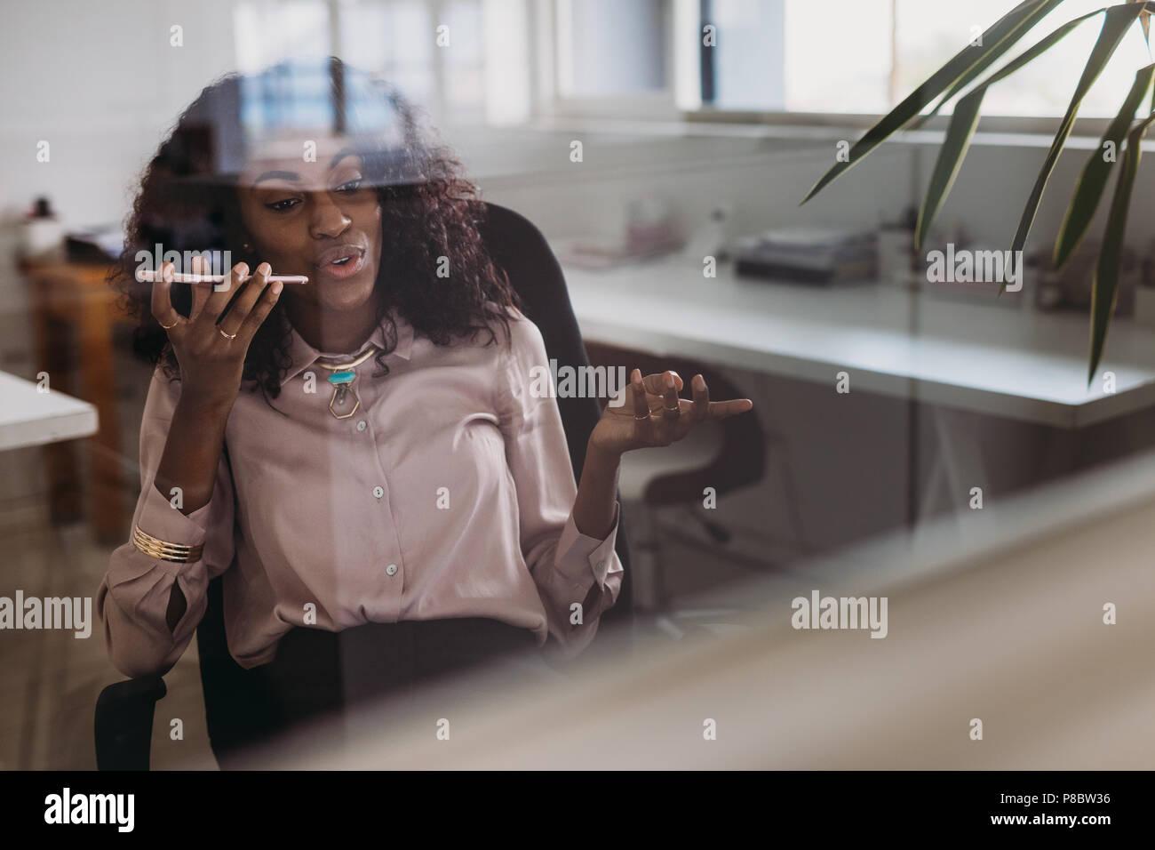 Imprenditrice in abbigliamento formale a parlare su telefono cellulare su altoparlante seduti a casa. Donna imprenditore managing business da casa discutendo wor Immagini Stock