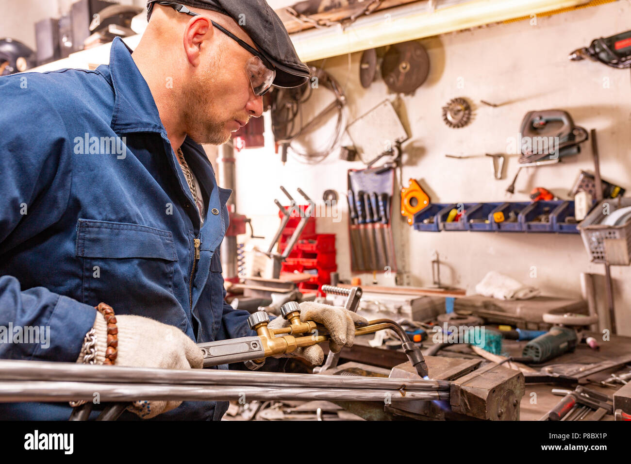 Il giovane uomo è andando a tagliare un pezzo di metallo di saldatura autogena. Immagini Stock