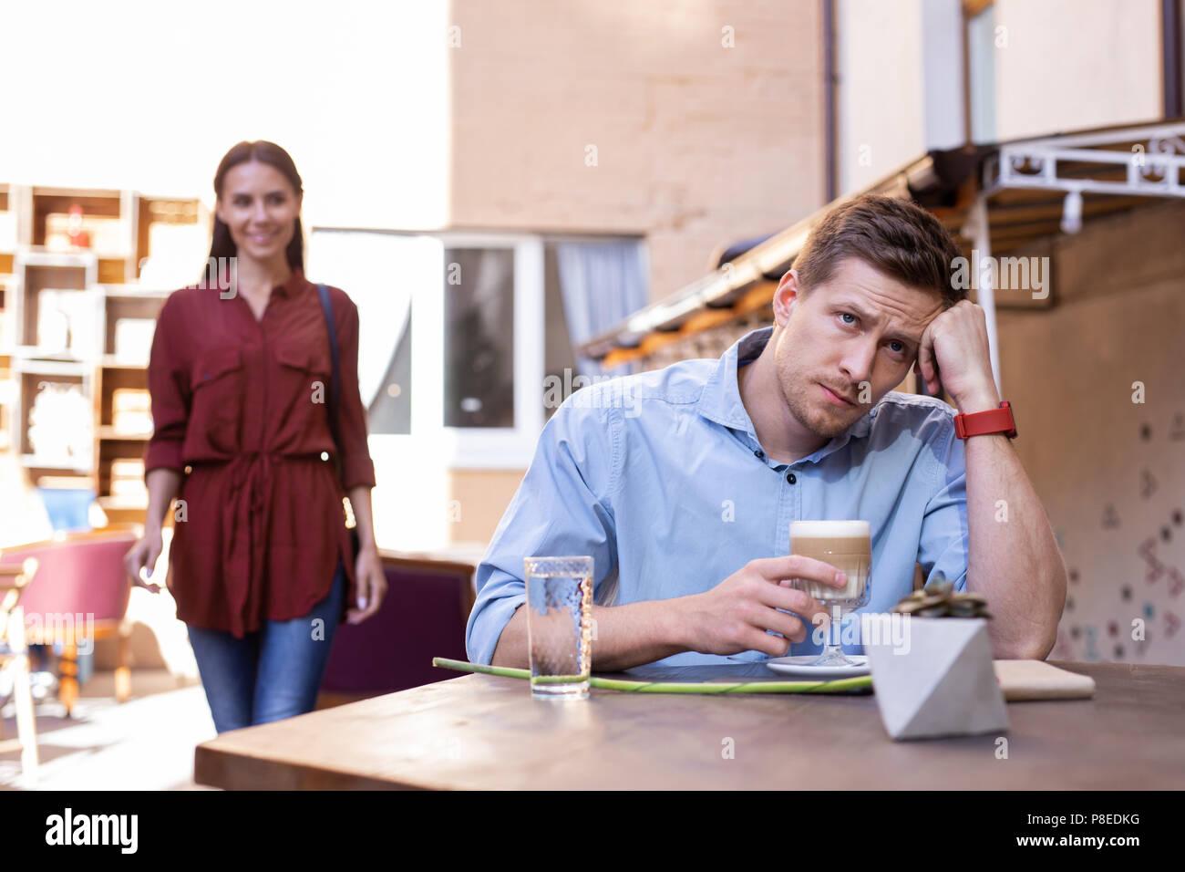Uomo bello sentirsi stanco di attesa per la sua ragazza per il pranzo Immagini Stock