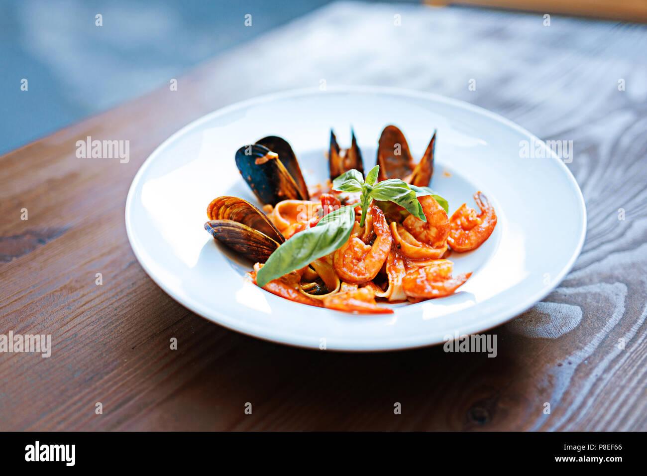 Close up di deliziosi piatti di pasta con alcuni piatti di pesce in salsa di pomodoro Immagini Stock