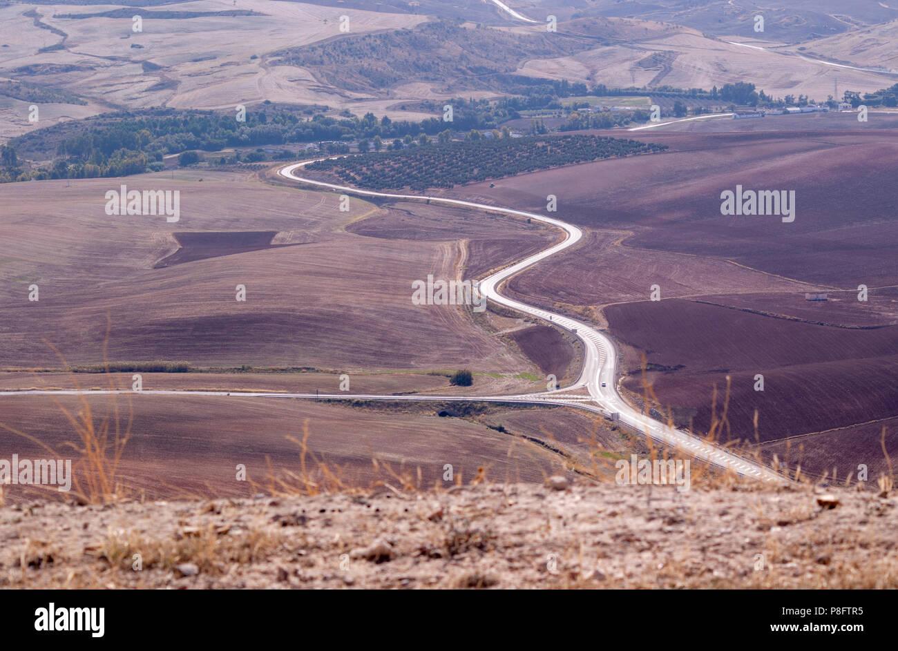 Vista da Teba al Distretto del Lago in Spagna. Andando su strada attraverso campi arida e oliveti Immagini Stock