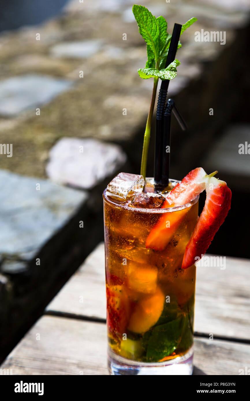 Un Pimm's in un bicchiere su un tavolo di legno - un rametto di menta come una struttura ad albero Immagini Stock