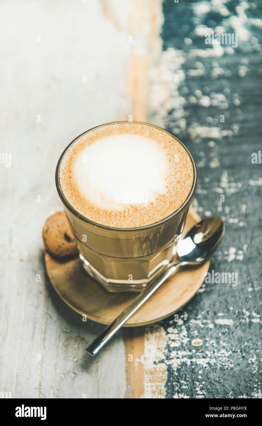 Classico cappuccino schiumoso caffè in vetro su tavola in legno rustico sfondo Immagini Stock