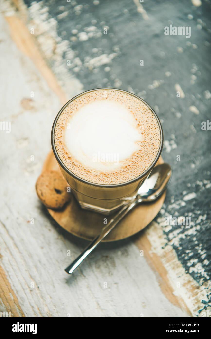 Classico cappuccino schiumoso caffè in vetro su tavola in legno rustico sfondo, vista dall'alto, il fuoco selettivo Immagini Stock