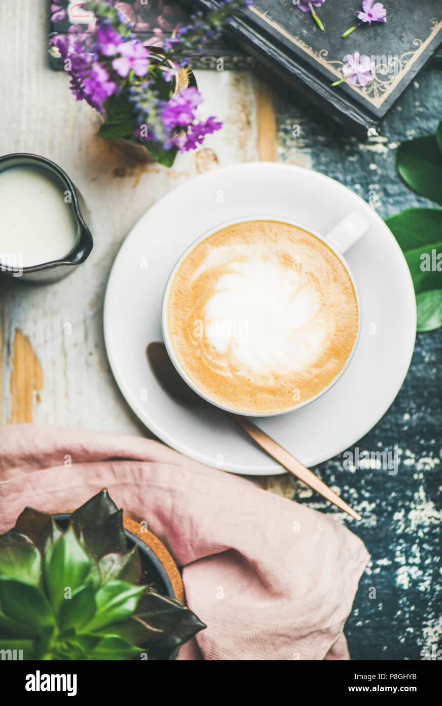 Classico cappuccino schiumoso caffè nella tazza di latte e fiori su tavola in legno rustico sfondo, vista dall'alto Immagini Stock