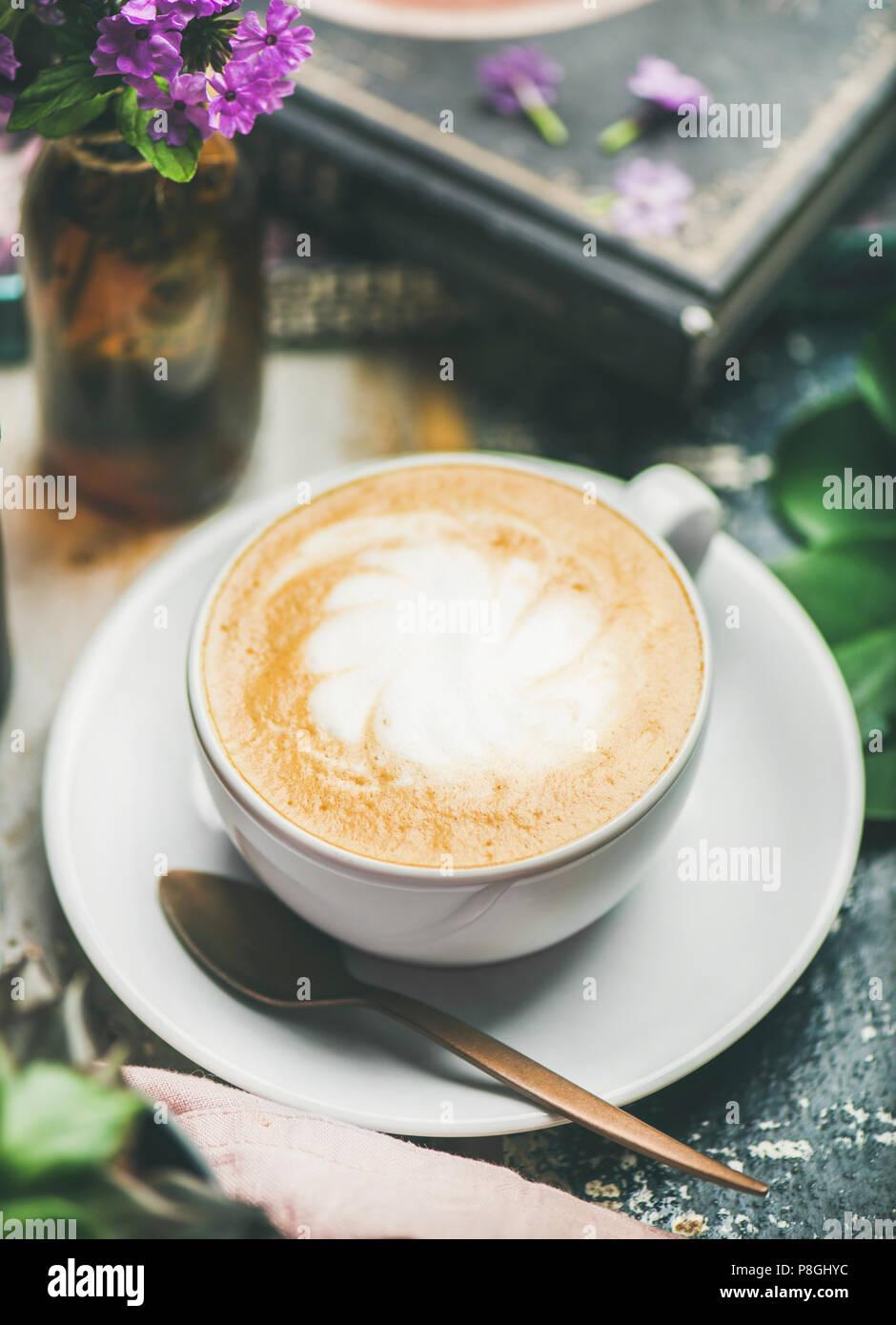 Classico cappuccino schiumoso caffè nella tazza con fiori su tavola in legno rustico sfondo, il fuoco selettivo Immagini Stock