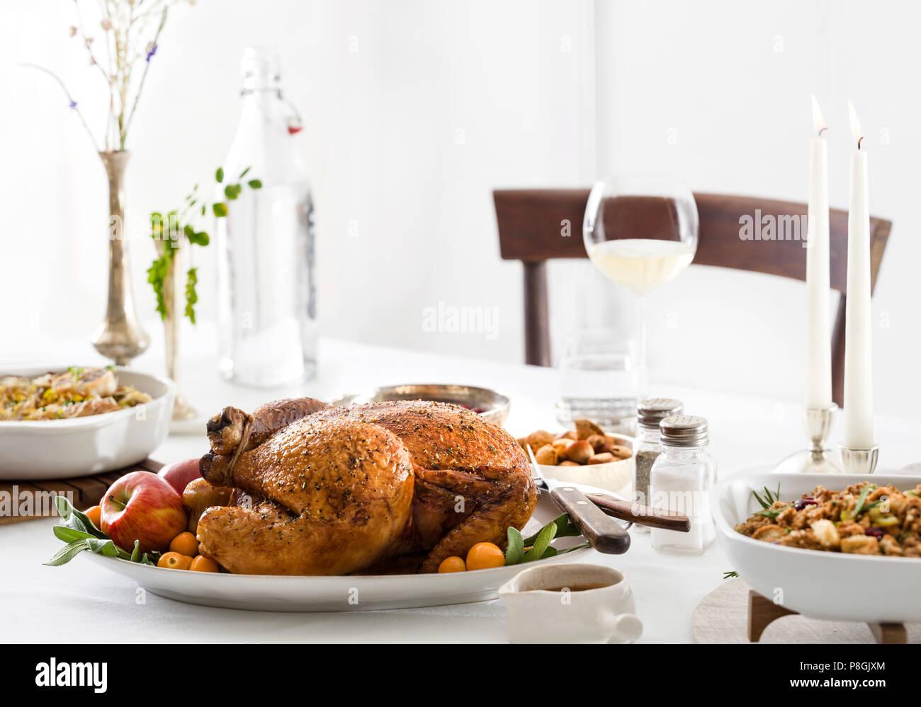 Una bella, pollo arrosto holiday cena su un pulito tavolo bianco con puliti, ancora rustico, impostazioni. Immagini Stock