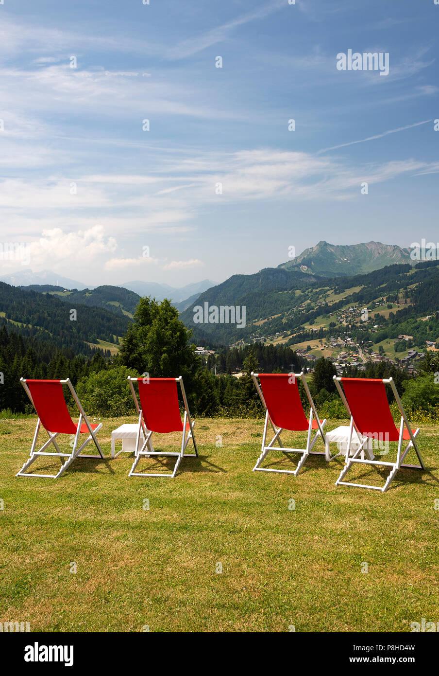 Rosso quattro sedie a sdraio nel giardino di Le Chasse-Montagne a Les Gets con viste sulla montagna in Haute Savoie Portes du Soleil Francia Immagini Stock