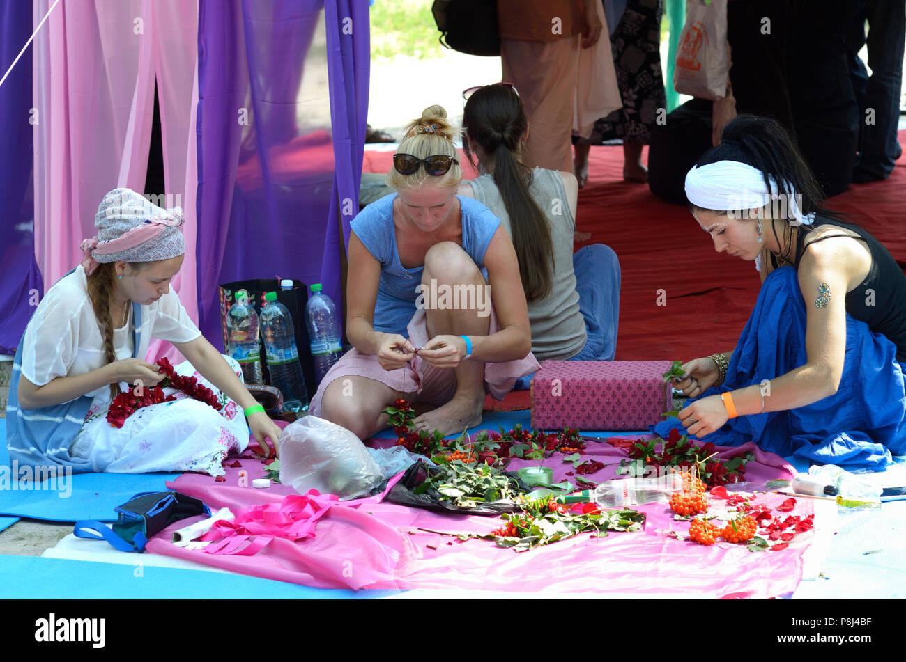 Donne vestito in abiti orientali seduta sul terreno e lavorare con fiori. Fest di cultura vedica Vedalife-2017. Il 7 agosto 2017. A Kiev, Ucraina Immagini Stock