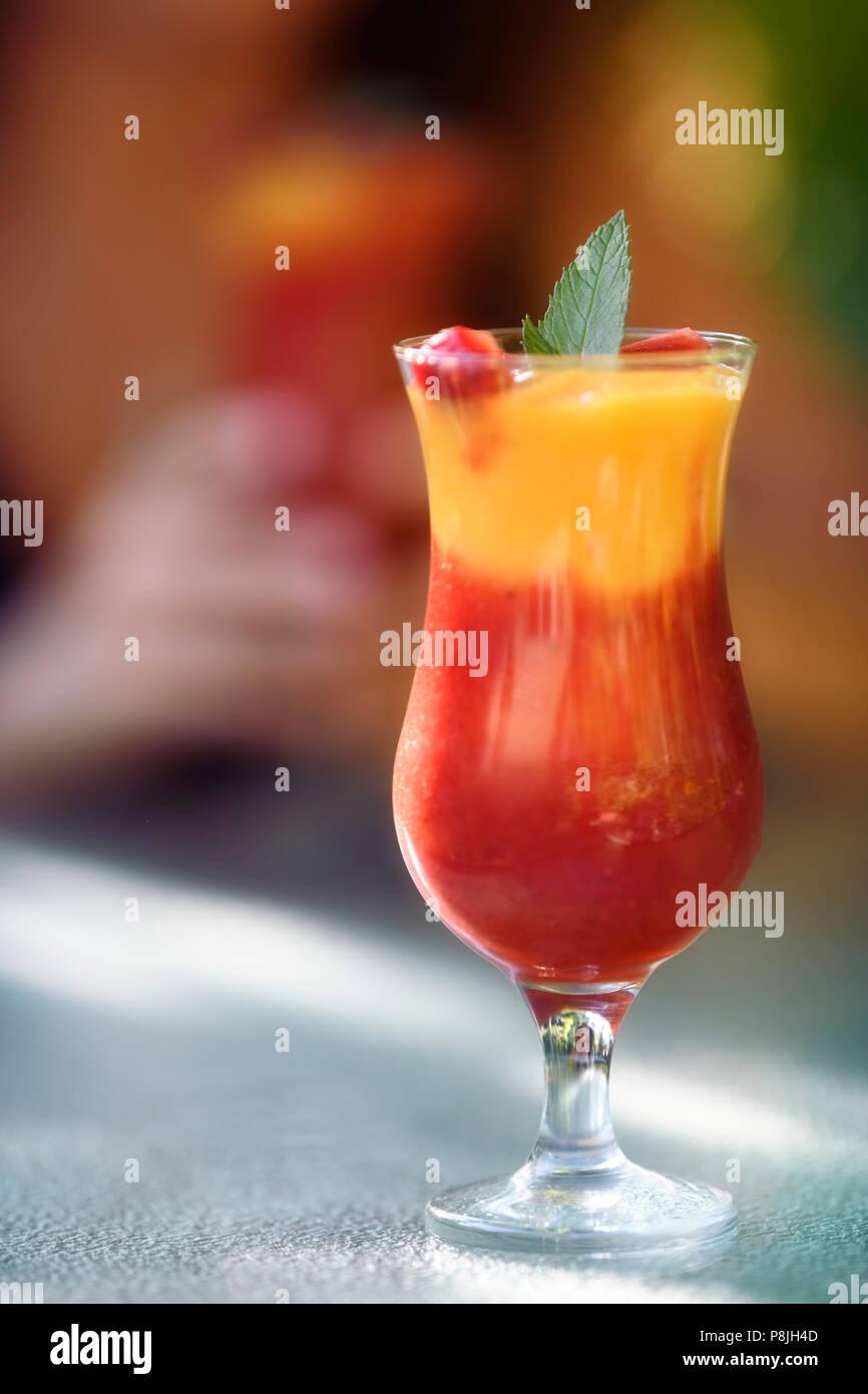 Vergine Strawberry Mango Margarita mocktail. Colorati cocktail analcolico, frullato di frutta bere su una tabella con una donna tenendo premuto un altro vetro in Immagini Stock