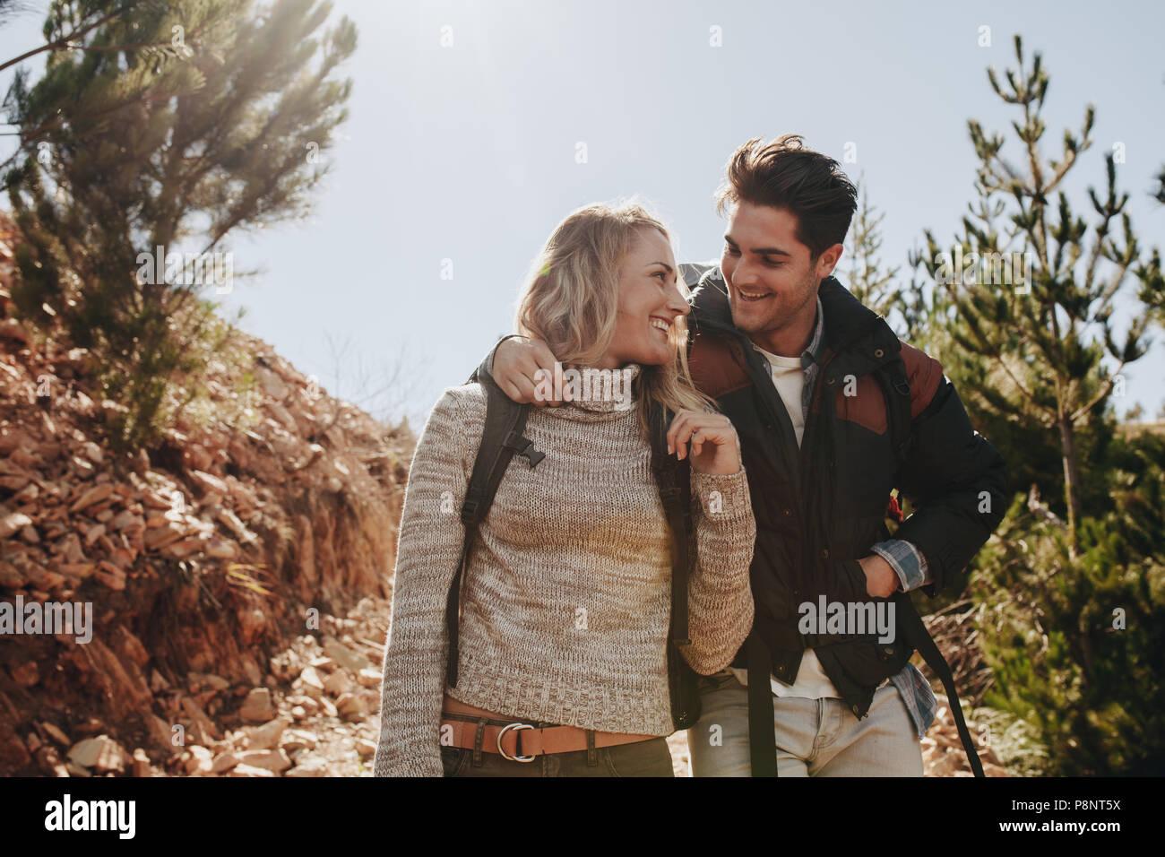 Matura in amore su una escursione in montagna. L uomo e la donna con zaino camminando sul sentiero di montagna e guardando ogni altra sorridente. Immagini Stock