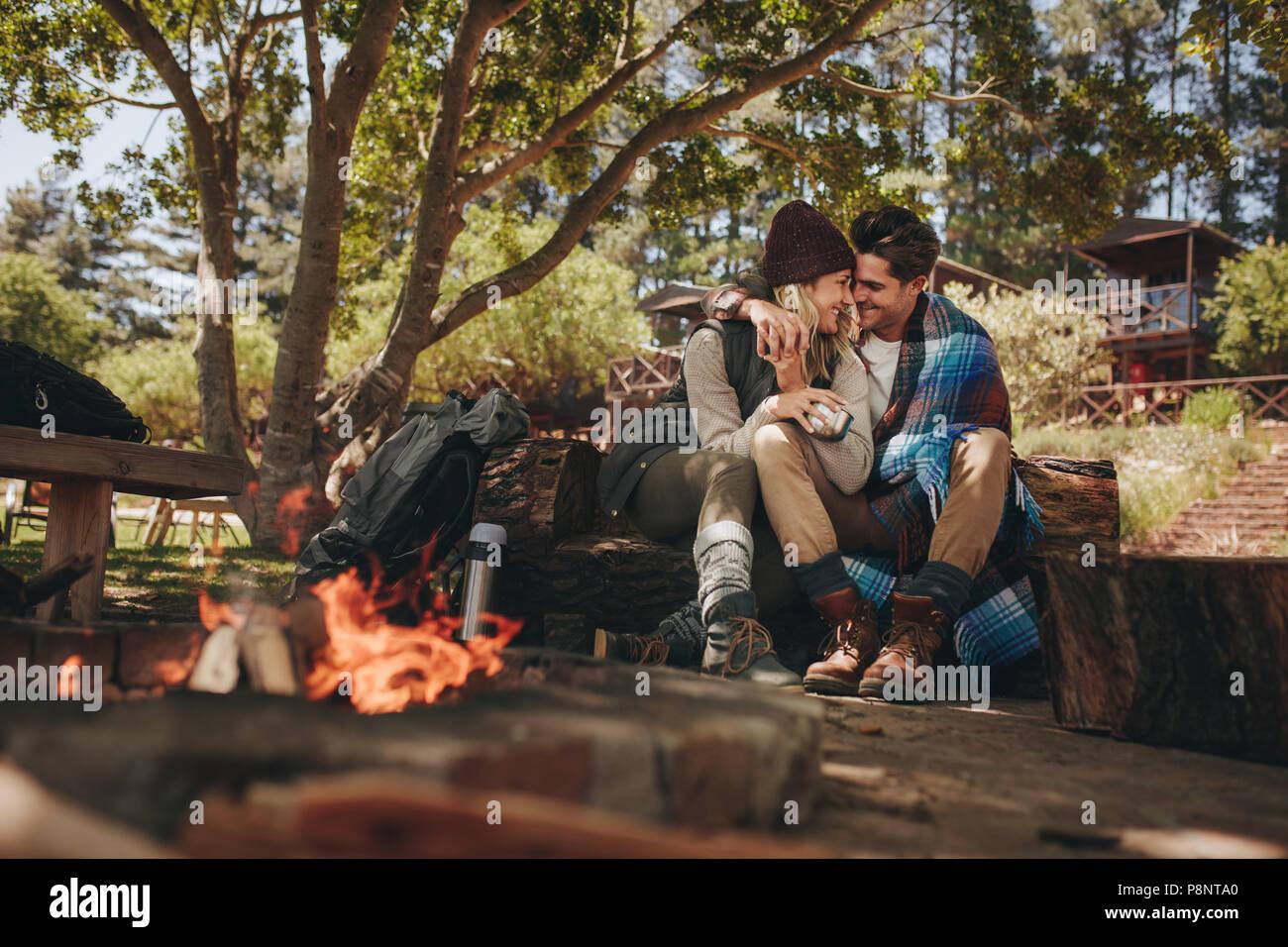Matura in amore seduta vicino a un falò al campeggio. L uomo e la donna sorpresa in un momento romantico al campeggio. Immagini Stock