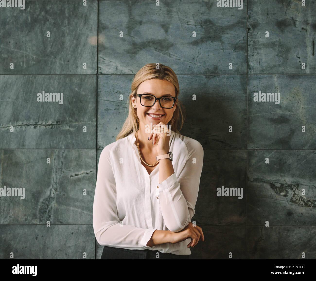 Ritratto di giovane e bella donna in abbigliamento formale in piedi contro il muro grigio e sorridente. Imprenditrice con gli occhiali guardando la fotocamera con la mano su chi Immagini Stock
