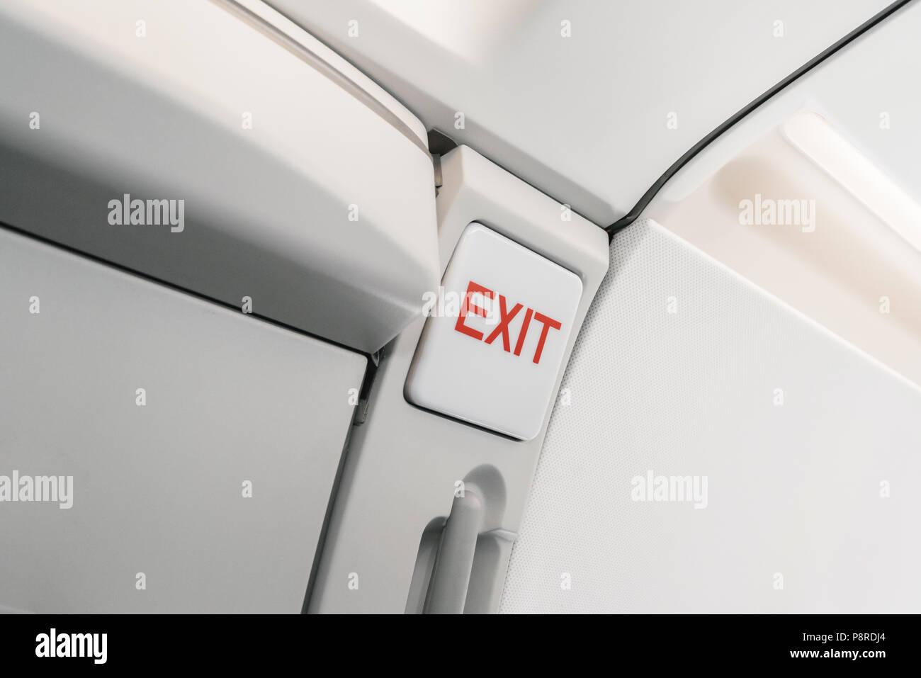 Uscita di emergenza segno su aereo. Vuoto aereo sedi nella cabina. Moderno concetto di trasporto. Aeromobili a lunga distanza di volo internazionale Immagini Stock