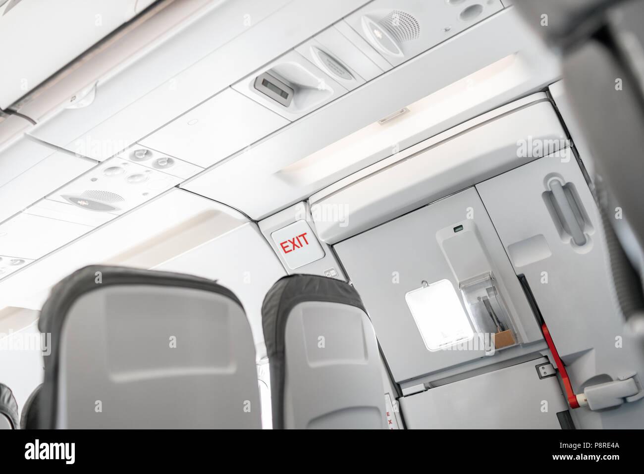 Uscita di emergenza a bordo di un aeromobile, vista dall'interno del piano. Vuoto aereo sedi nella cabina. Moderno concetto di trasporto. Aeromobili a lunga distanza di volo internazionale Foto Stock
