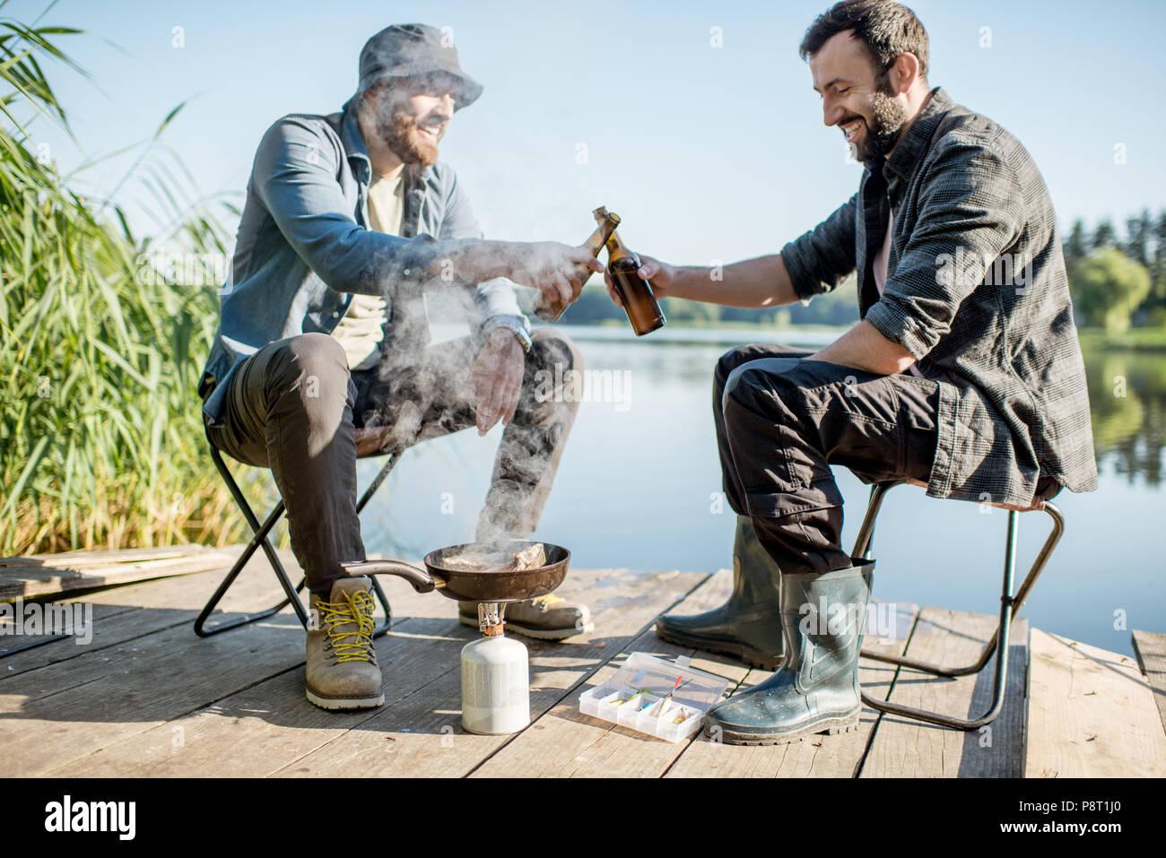 Due pescatori la frittura di pesce con seduta birra durante il picnic sul molo in legno vicino al lago al mattino Immagini Stock
