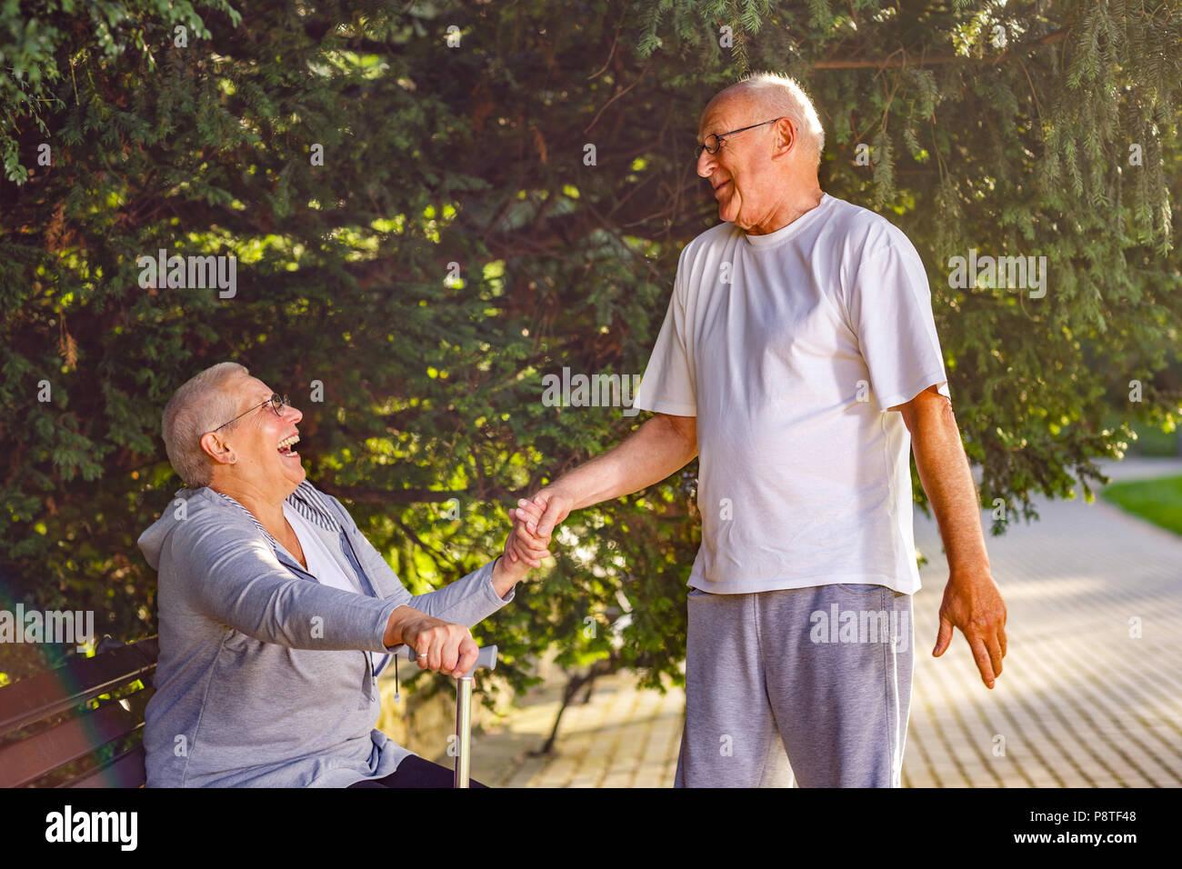 Gli anziani nella park- sorridente uomo vecchio caring moglie nel parco Immagini Stock