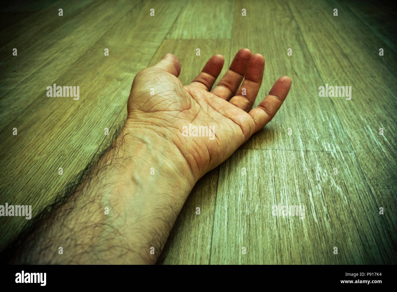 Maschio di mano e il braccio disteso sul pavimento, morto Immagini Stock