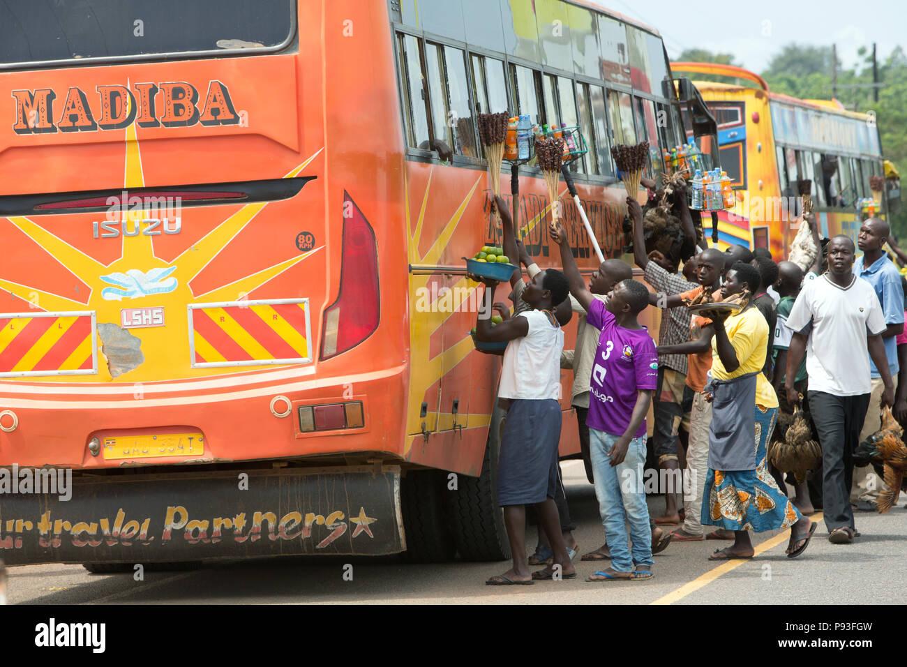 """Kamdini, Uganda - ad una fermata del bus, battenti mercanti offrono ai viaggiatori un """" commuter """" bus per la vendita. Immagini Stock"""