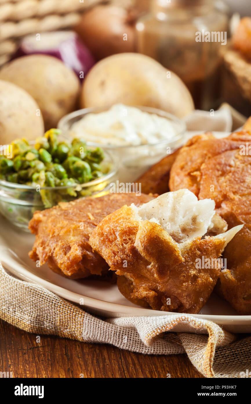 Il tradizionale pesce in pastella di birra e patatine con pisello verde e salsa tartara Immagini Stock