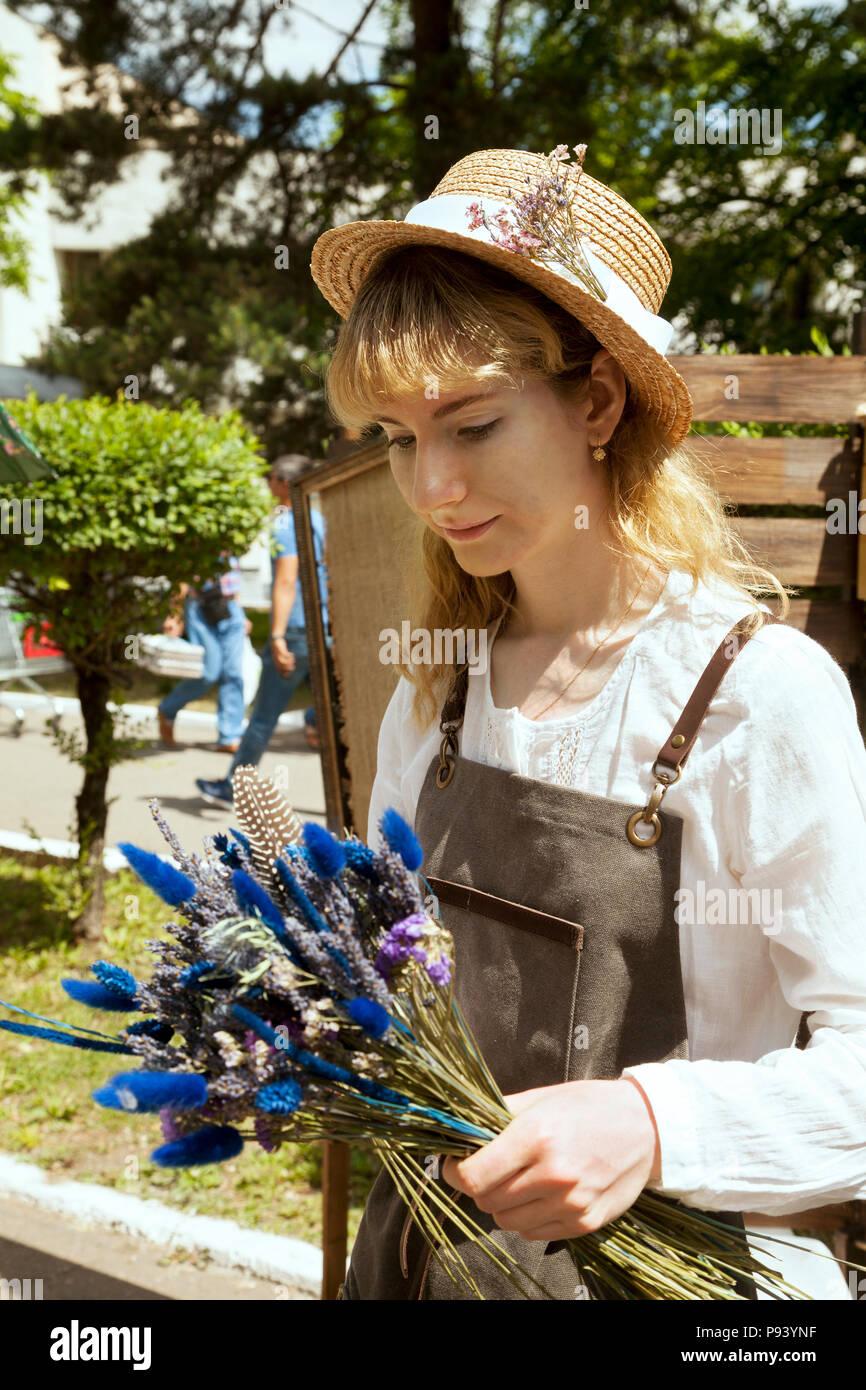 Giovane donna che indossa il contadino vestito e azienda bouquet di fiori di  campo. Bella ragazza pastorale in un cappello di paglia e grembiule con  lavanda ... c4b4127bcb69