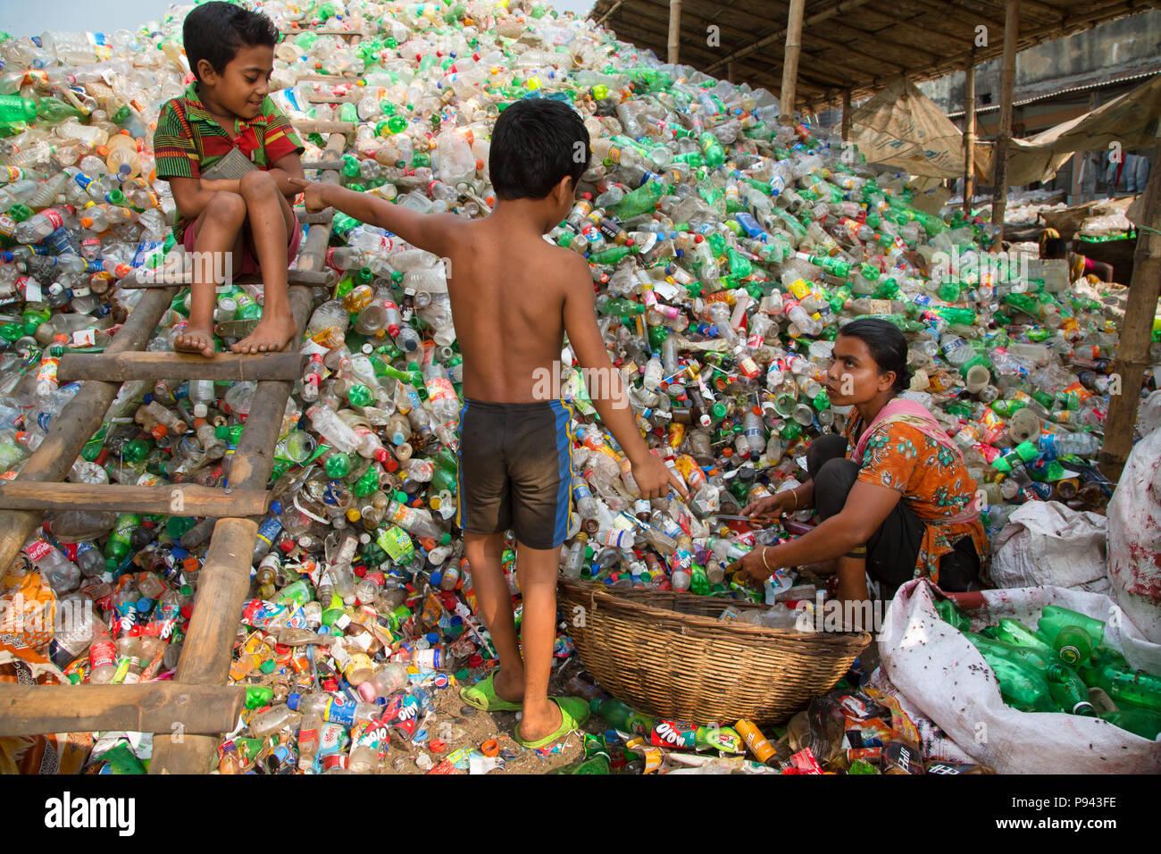 La madre lavora nel riciclaggio di plastica nella factory di Hazaribagh, Dacca in Bangladesh Immagini Stock
