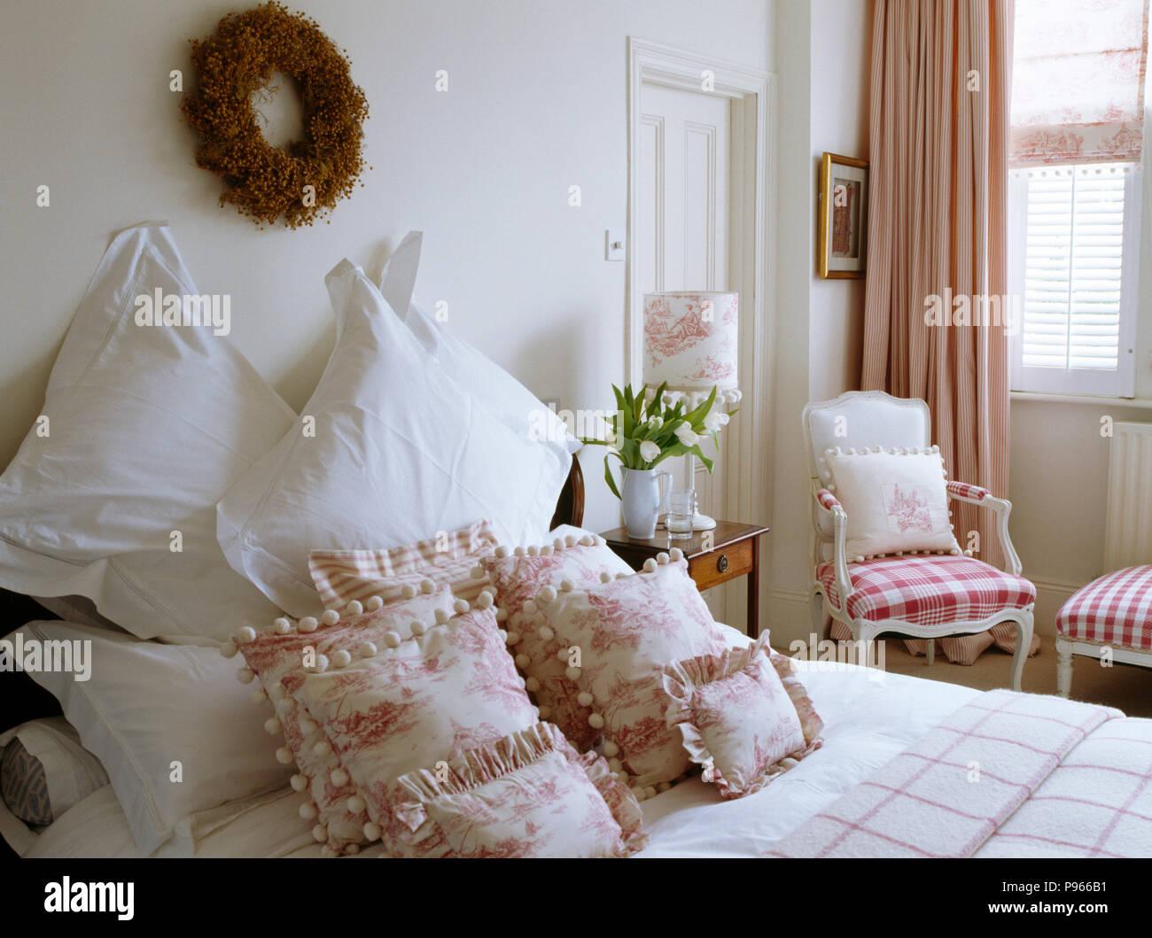 Rametto corona sopra il letto con cuscini bianchi e rosa bianca