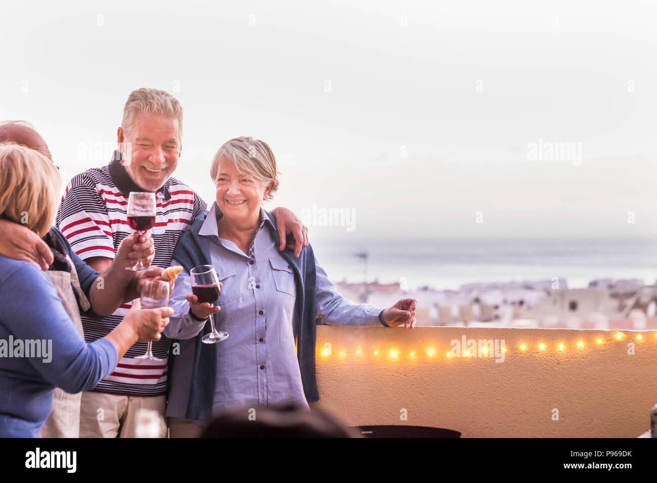 Evento di celebrazione all'aperto per un gruppo di persone adulte. drkinking vino nella terrazza sul tetto con una bella vista sullo sfondo. Lo stile di vita felice togethe Foto Stock