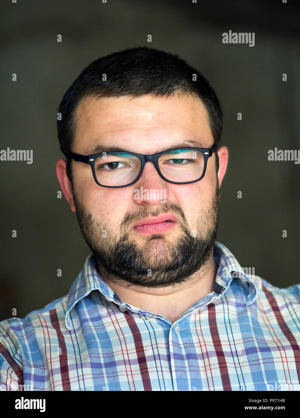 Ritratto di bello barbuto dai capelli neri moderno intelligente giovane in  bicchieri con taglio di capelli corti e tipo neri occhi sorridenti nella ... b3dfc7950f08