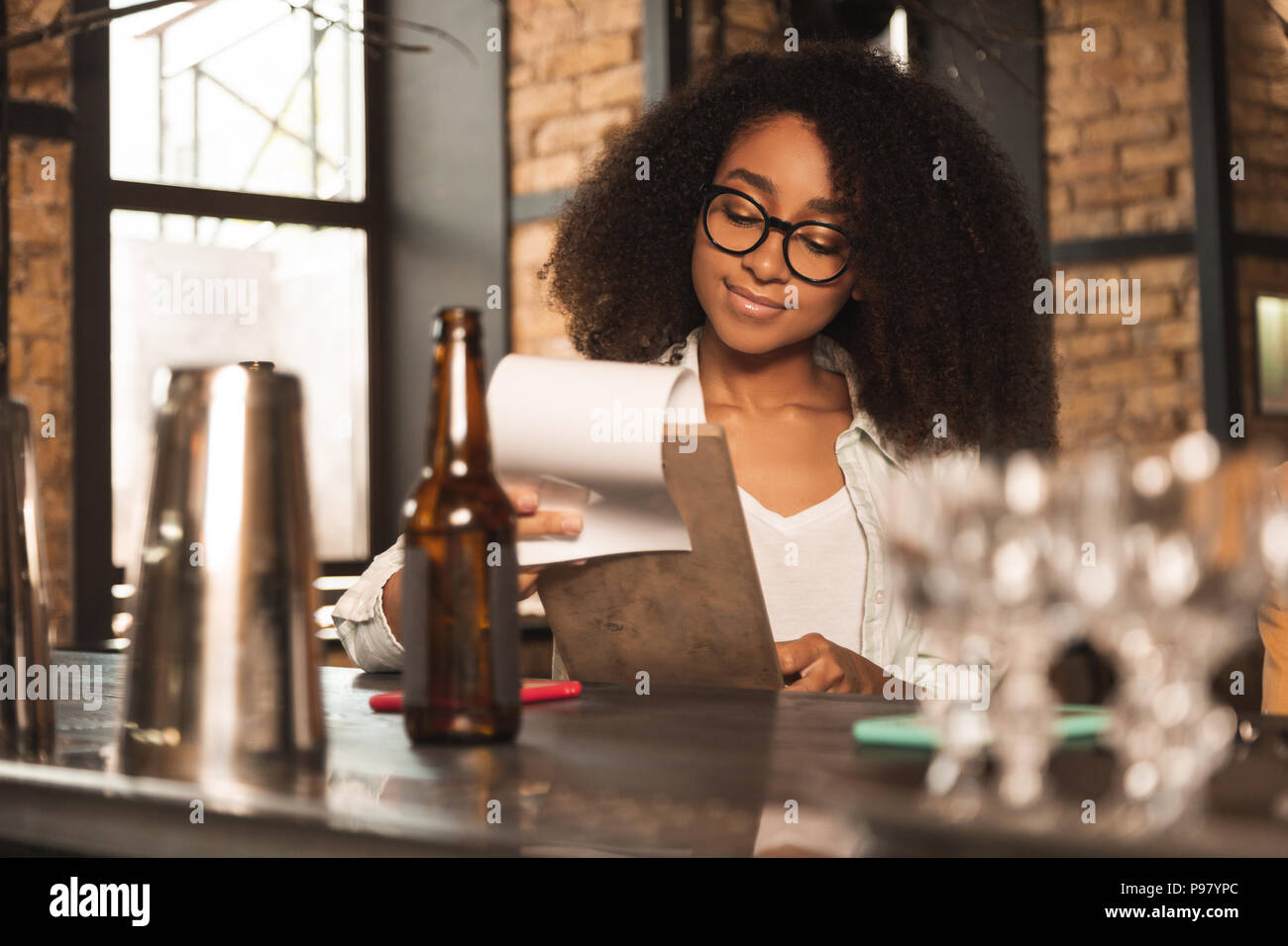 Bella donna ricci guardando attraverso il menu in pub Immagini Stock