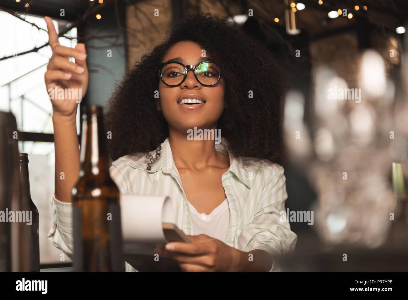Upbeat curly donna ponendo fine al bar Immagini Stock