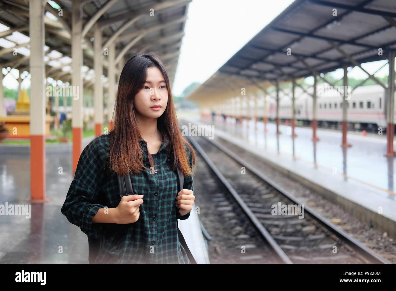 Aisan donna aspettando il treno in stazione con Tavel concetto. Immagini Stock