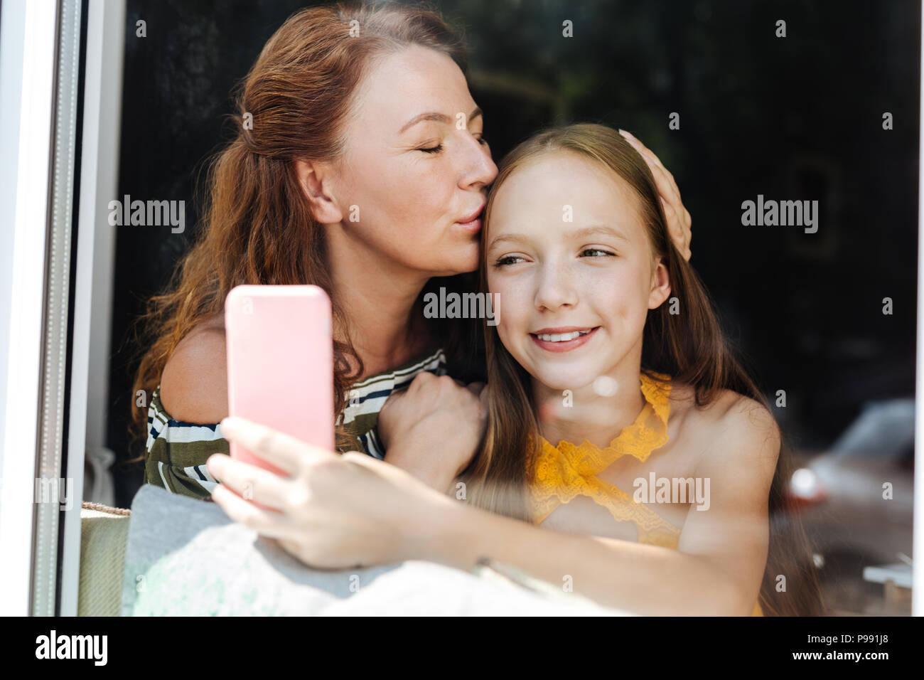 Amorevole Madre bella baciando la sua amorevole figlia Immagini Stock