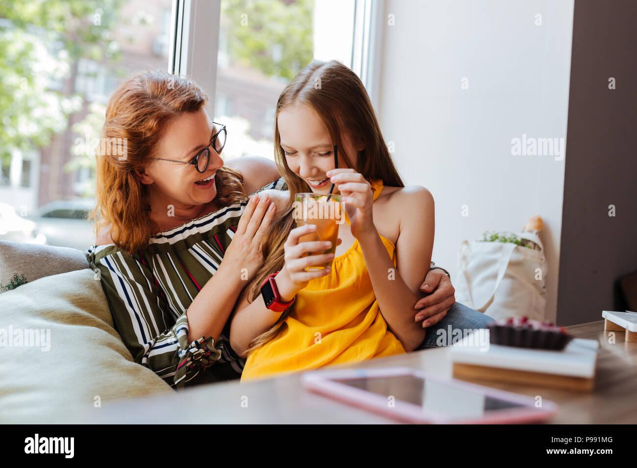 Bionda figlia sorridente bevendo cocktail Immagini Stock