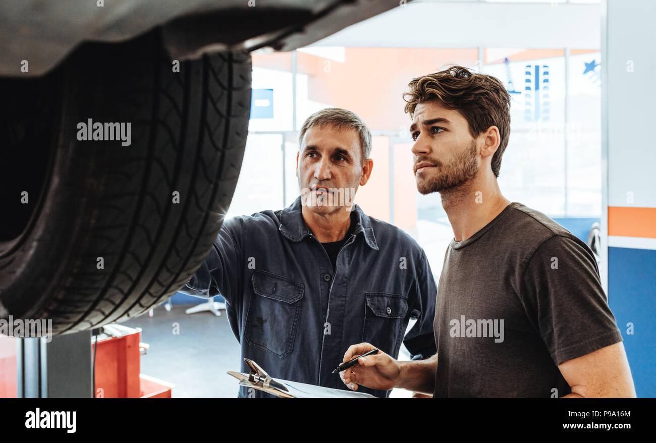 Due auto professionisti del servizio di controllo di una macchina sollevata sulla rampa e rendere note. La meccanica di ispezionare la macchina in officina di riparazione. Immagini Stock