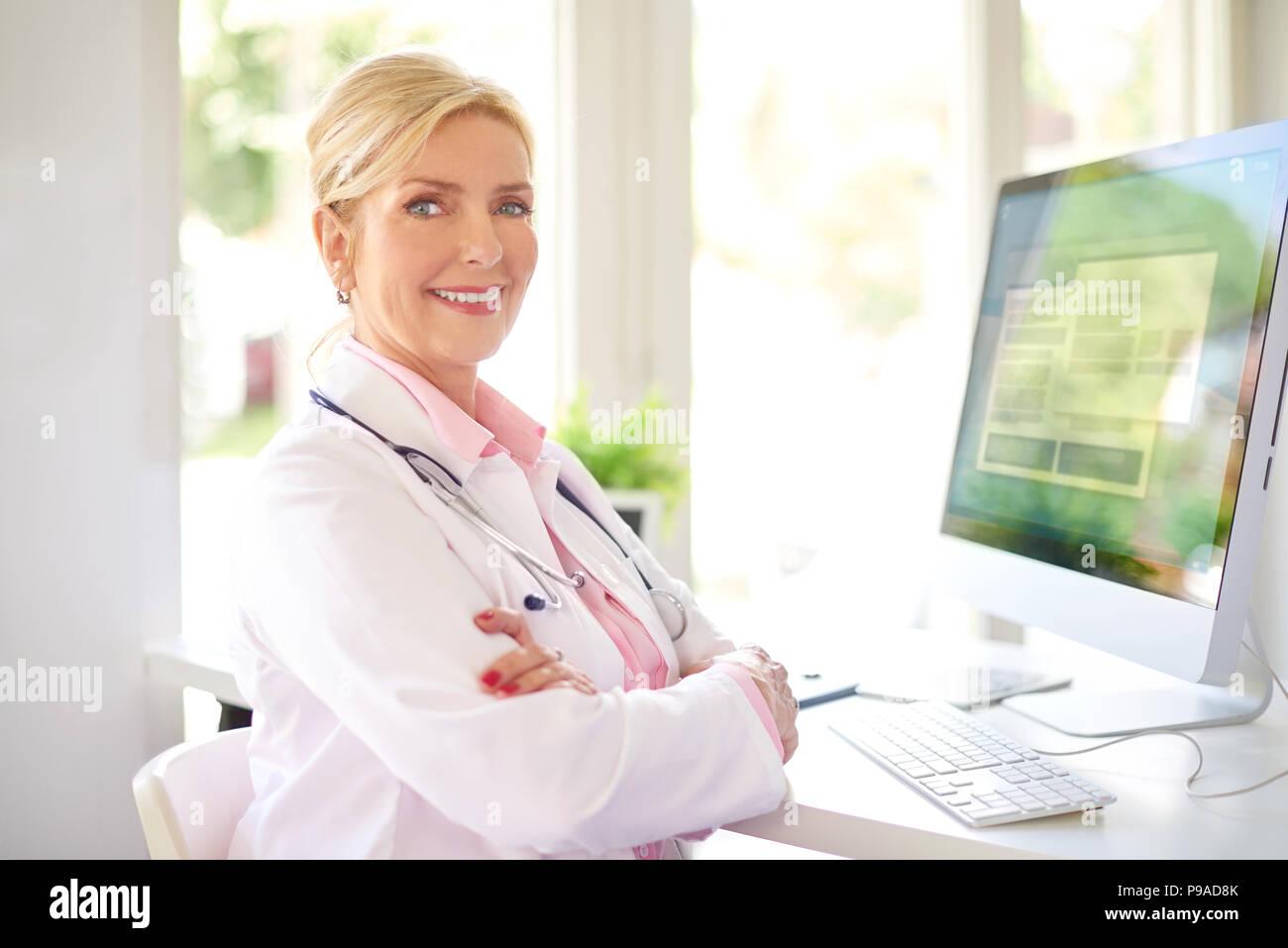 Bella donna sorridente ricerca medico seduto davanti al suo computer presso l'ufficio del medico e di lavoro. Immagini Stock
