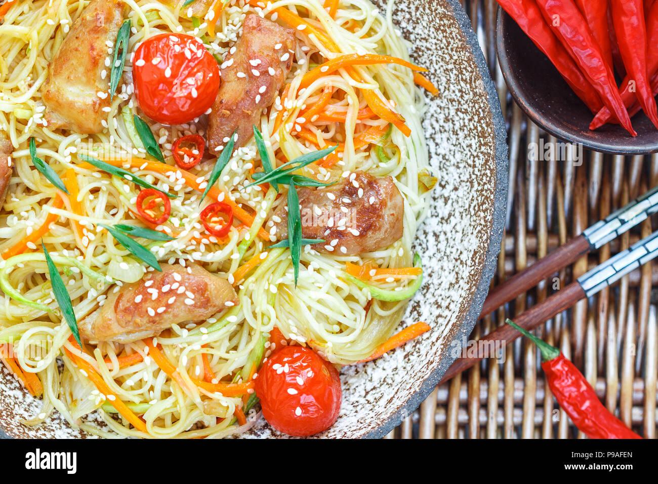 Saltate in padella a base di noodle con pollo e verdure (carote, pomodori, zucchine, aglio, pepe rosso, cipolla verde), semi di sesamo e salsa di soia sulla piastra di argilla vicino Immagini Stock