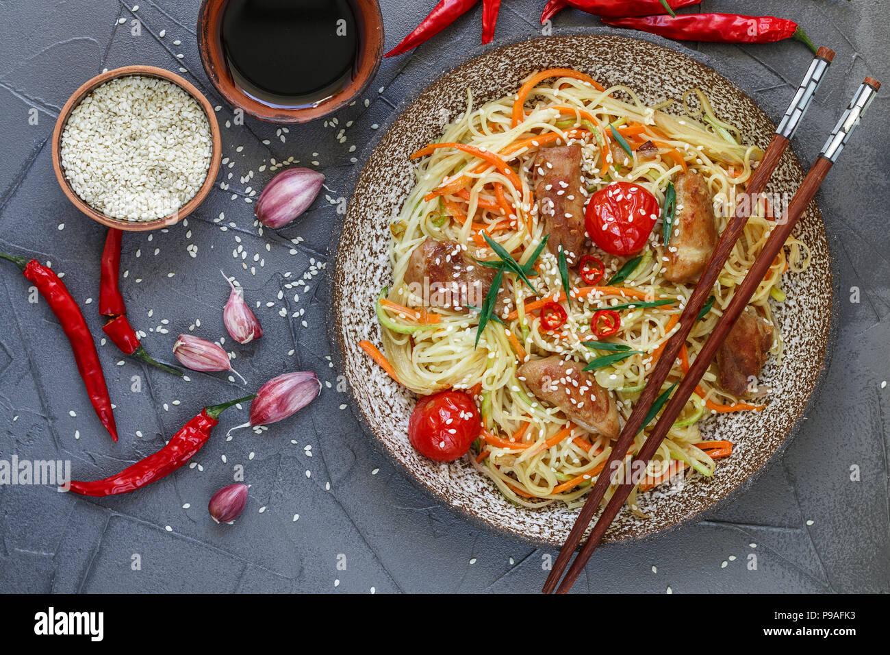 Saltate in padella a base di noodle con pollo e verdure (carote, pomodori, zucchine, aglio, pepe rosso, cipolla verde), semi di sesamo e salsa di soia sulla piastra di argilla. Asian Immagini Stock