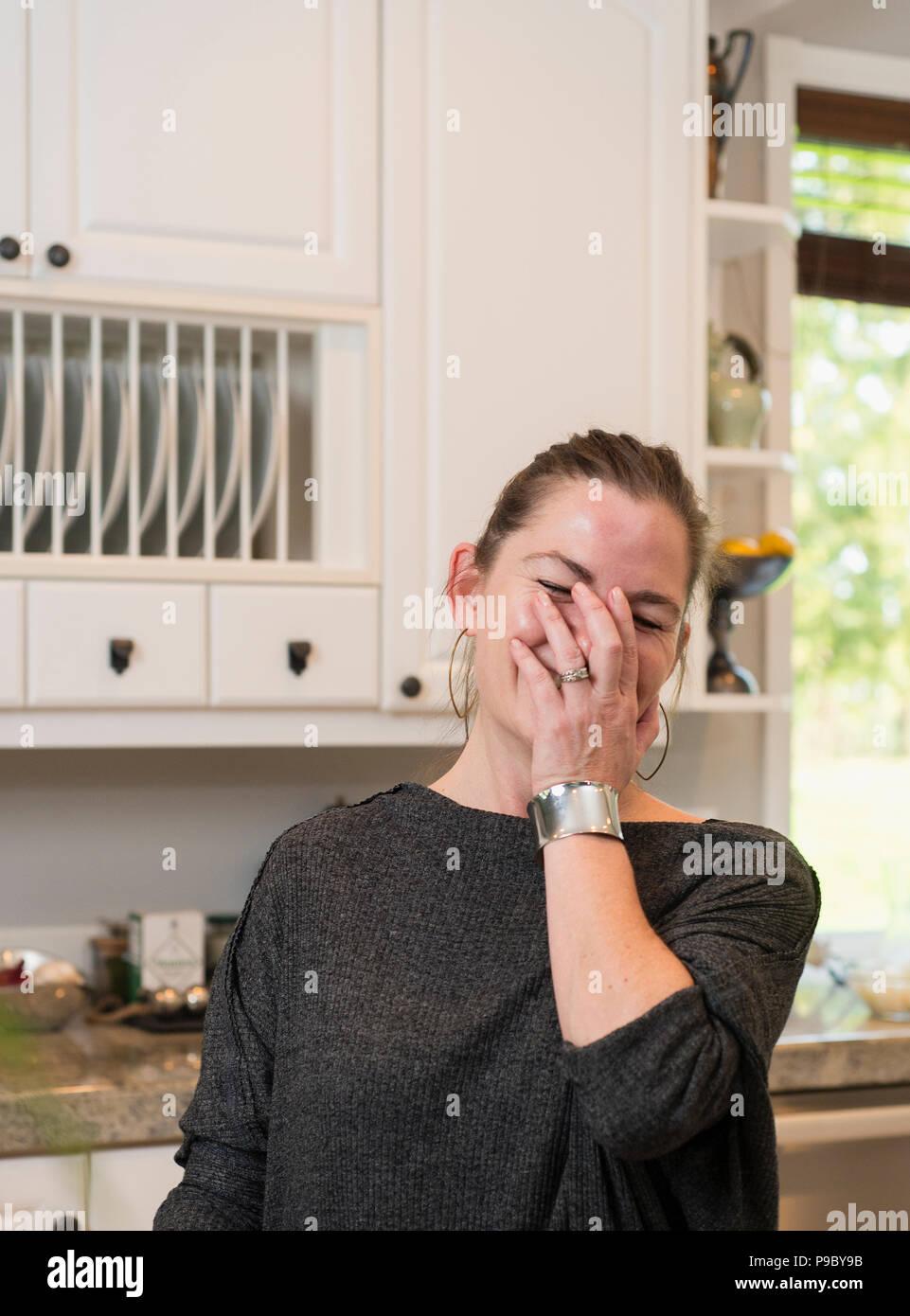 Una donna che ride nella sua cucina. Immagini Stock