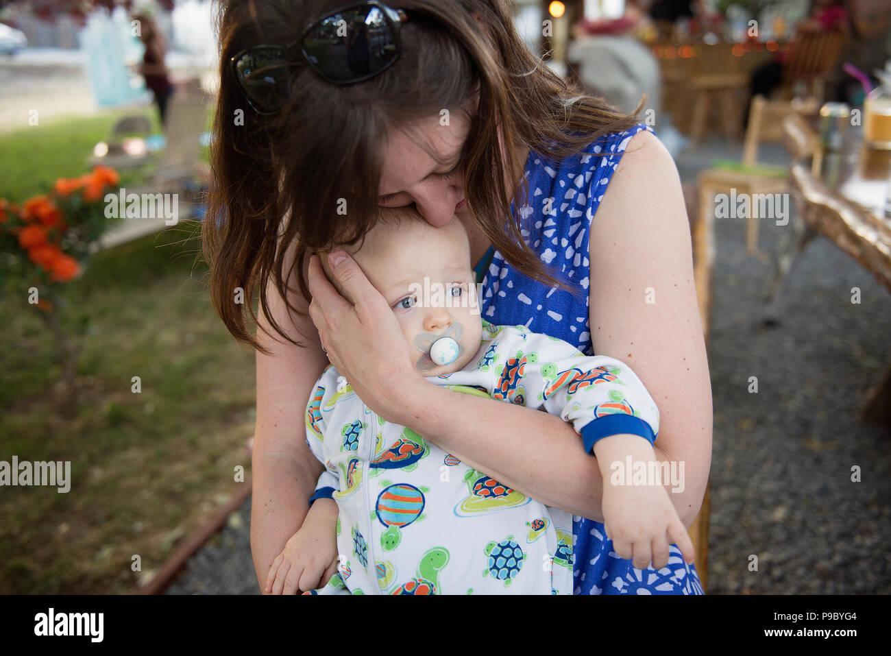 Una madre che abbraccia il suo un anno di età bambino. Immagini Stock