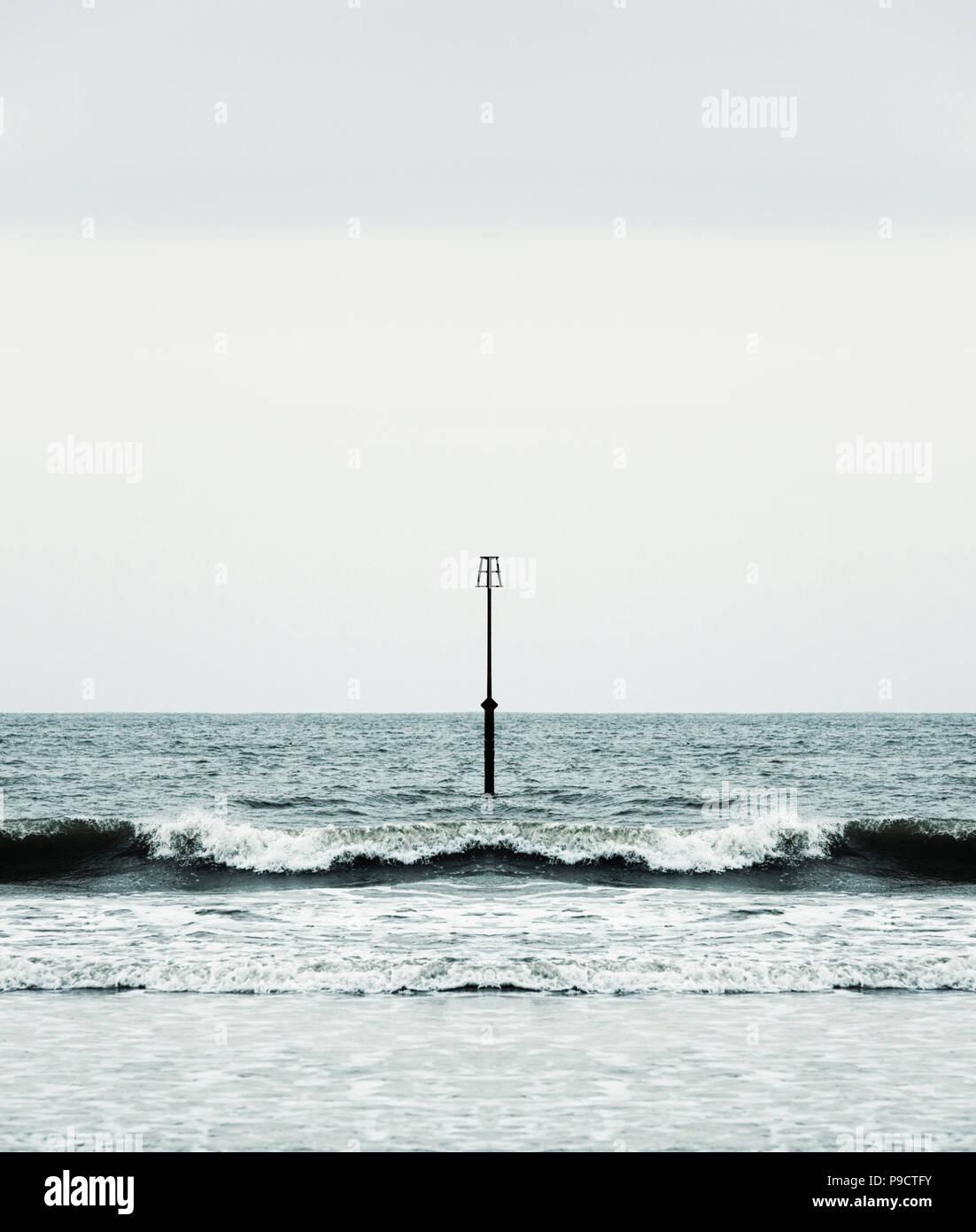 Onde e surf rompe su una spiaggia attorno a un faro groyne, England Regno Unito - Concetto di simmetria Immagini Stock